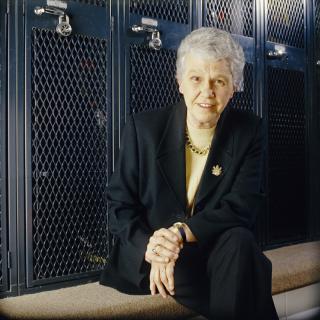 Dr. Christine Grant poses in a locker room.