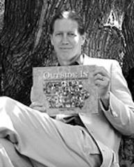 A man sitting by a tree holding up book