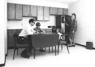 Black-and-white photo of a family in the kitchen at Hawkeye Court apartments circa 1968