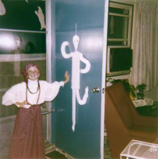 Color photo of young Jennifer Wilkins in costume, standing by an open door at Hawkeye Court Apartments on Halloween, circa 1978