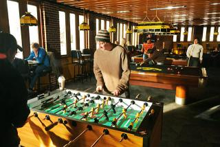 Color photo of students playing foosball and pool in the student union