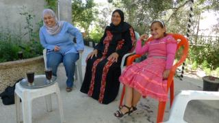 two women and a young girl in Palestine sit in chairs dressed in traditional clothing