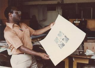 Leon Hicks looking at a print.