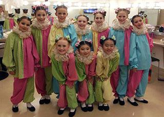 10 young gilrls dressed as clowns in a dressing room