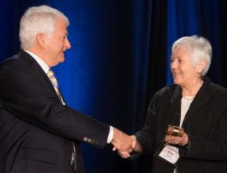 Outgoing A.P.L.U Board Chair Gene D. Block passes the gavel to UI President Sally Mason