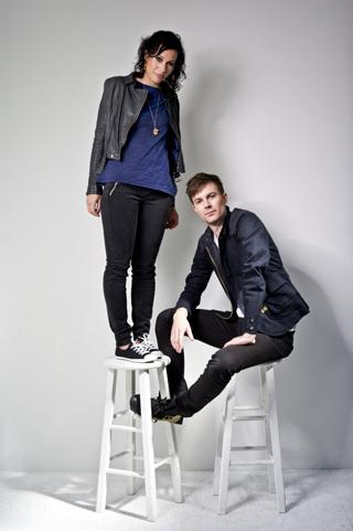 woman standing on a stool next to man sitting on a stool