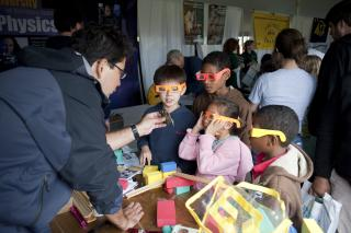 "During the 2011 iExploreSTEM event, Larry Escalada, Ph.D.,  University of Northern Iowa professor of physics and science education, shows children how to compare light patterns of different light emitting devices using ""rainbow glasses."" These glasses appear to have scratches that actually are diffraction gratings used to breakdown light so the entire light spectrum can be observed."