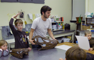 Museum studies certificate student Andrew Blodgett teaches local kids about dinosaurs at the University of Iowa Museum of Natural History.