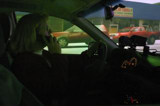 Female driver talking on phone in driving simulator