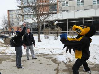 two students toss a paper cup into a recycle bin held by Herky