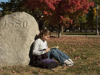 Student sitting on the Pentacrest by the 1880 boulder
