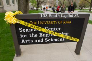 Phil Was Here caution tape wrapped around a campus building sign