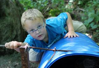 A young boy crawls on top of a blue tube at a UI Wildlife Camp