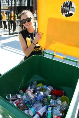 Rachel Price shows cans and bottles collected for recycling at Gate I outside Kinnick Stadium