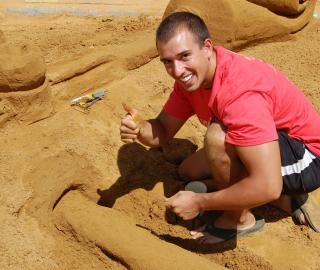 Delta Sigma Delta member Brad Adams gives thumbs up as he works on the fraternity's sculture for Sand in the City