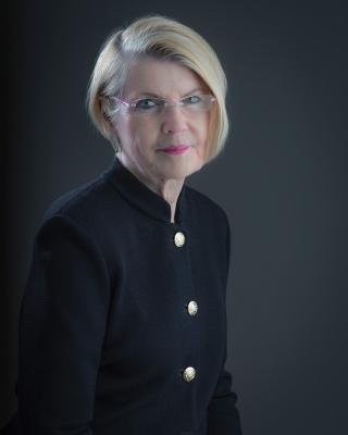 A photo portrait of a blonde woman with a black blouse.