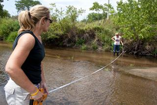Kathy Geers and Angie Alzheimer measure the width and depth of a creek that flows into the Cedar River.