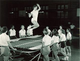 woman jumping on trampoline as other women stand around the trampoline