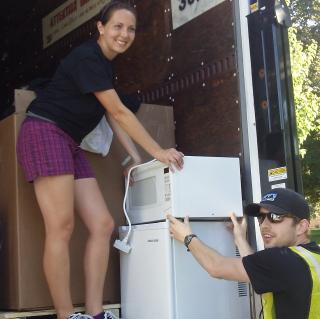 Andrea Uhl helps a volunteer load a microwave onto the Goodwill truck during last year's Donation Drive.