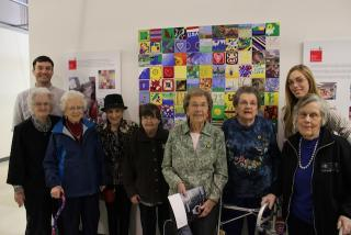 A group of people standing in front of artwork made up of painted tiles