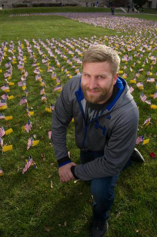 Logan Suhrbier kneeling before flag arrangement