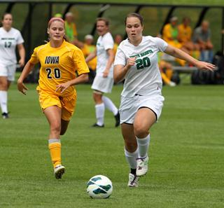 women's soccer players pursue the ball