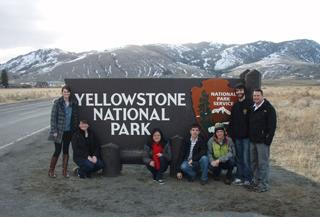 University of Iowa students standing beside a Yellowstone National Park sign