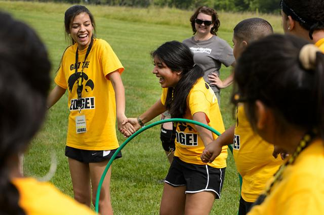 UI first-year students join hands to form a circle and must pass the hoop around without breaking their grip. Team building activities are designed to help participants in The Iowa Edge program build community with a group of peers before the semester beg