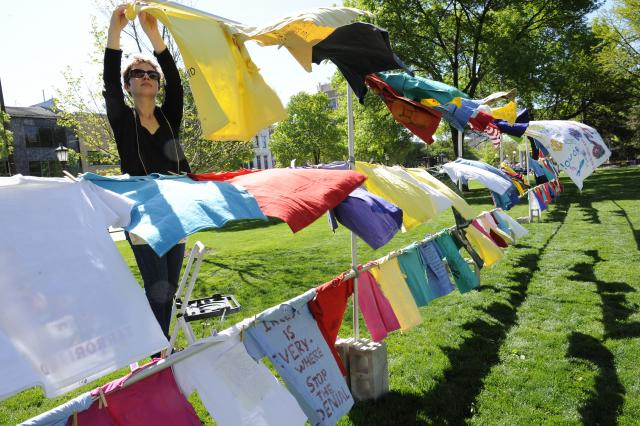 a woman hangs a t-shirt for the annual Clothesline project display