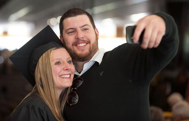 Graduate takes a photo on her phone