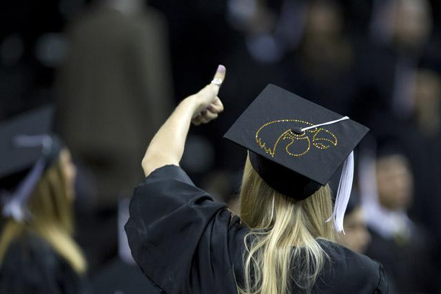a photo of a UI graduate giving a thumbs up wearing a graduation cap with Herky on the top