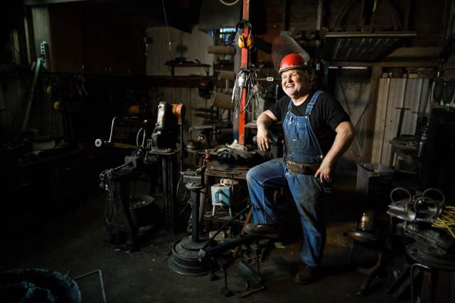 A man wearing blue overalls and a red hard hat posing with a smile in a room filled with metalworking equipment.