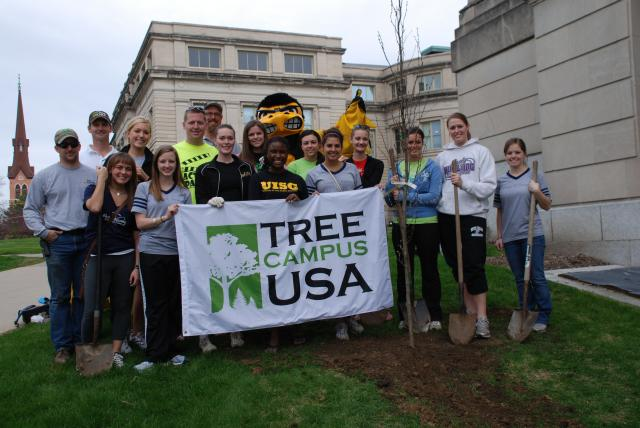 students, staff pose with Herky and the Tree Campus banner