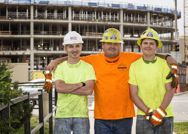 Three men in hardhats pose in front of a construction site.
