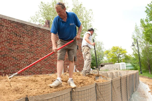 Workers fill HESCO barriers with sand.