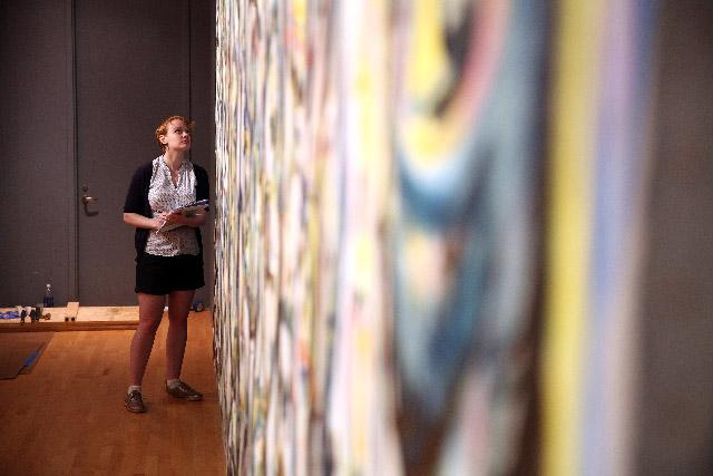 curator inspects Pollock's Mural