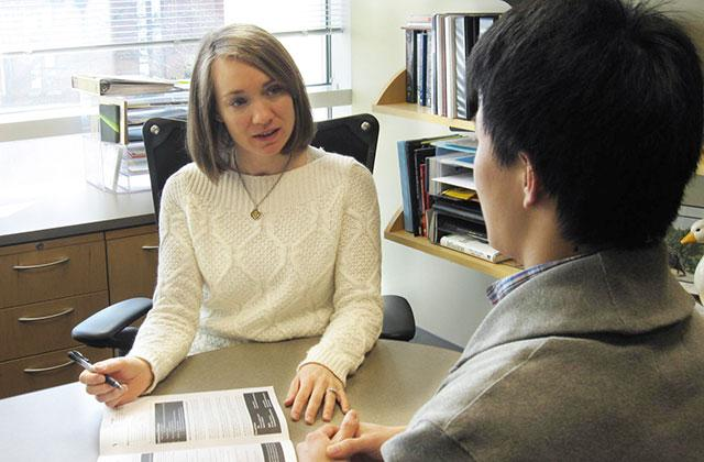 Amy A'Hearn talking with a student in her office