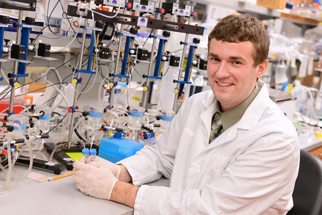 UI Student Employee of the Year, Andrew Michalski sits at a laboratory bench in the Eckstein Medical Researchh Building.