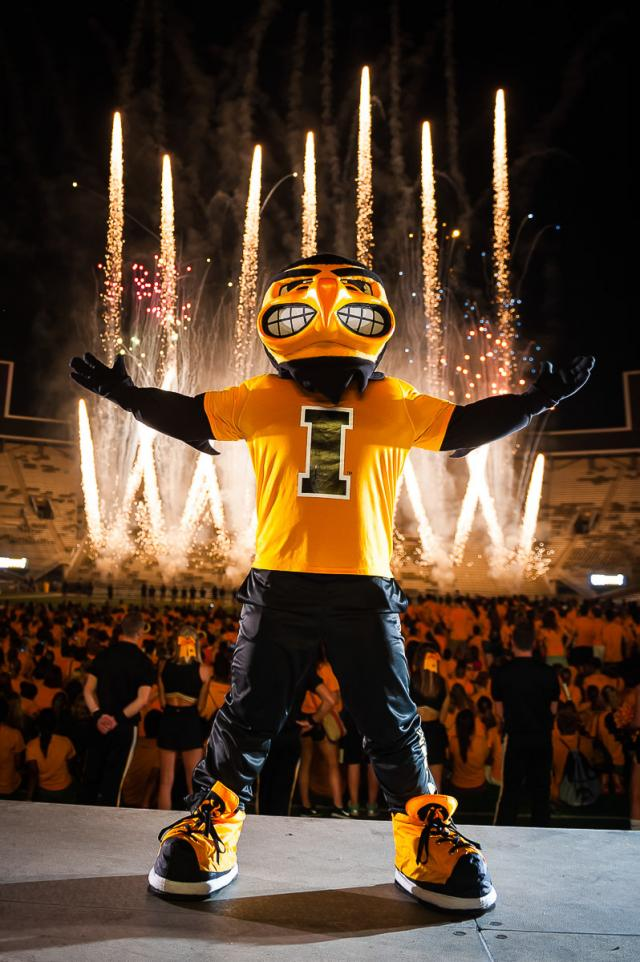 UI mascot Herky on stage with fireworks in the background
