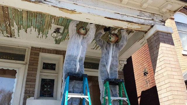 Guys scraping paint off a porch ceiling.