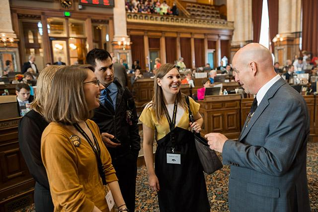 Four college students in business casual clothing talk with an older bald man in a suit.