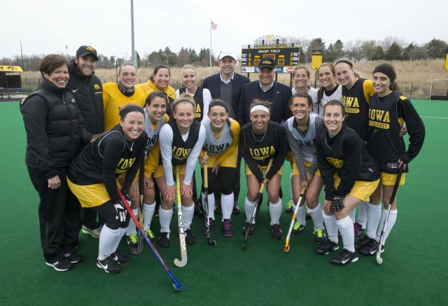 FIH President Leandro Negre presents an FIH pin to Natalie Cafone during their practice Wednesday, April 23, 2014 at Grant Field on the UI campus in Iowa City.