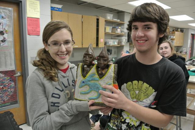 A high school girl and boy holding a example of African art