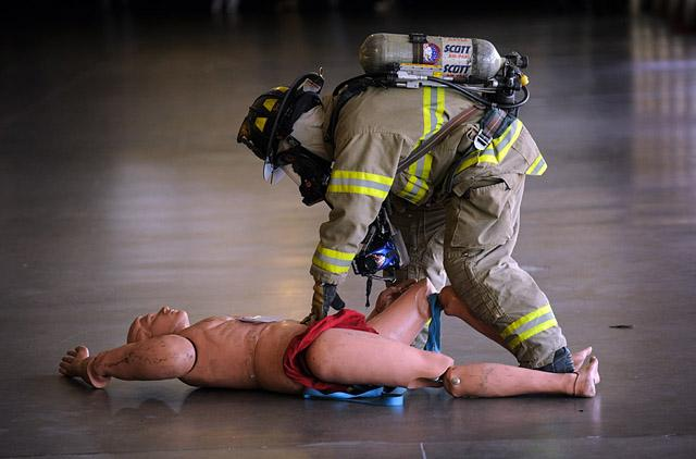 """A firefighter examines a """"dummy"""" victim."""