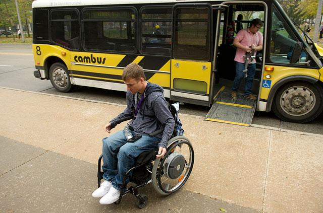 Travis wheels away from the bus he rode to class.