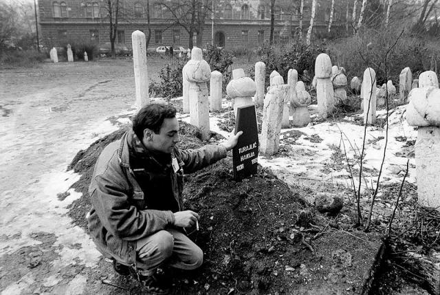 Man kneels by grave stones.