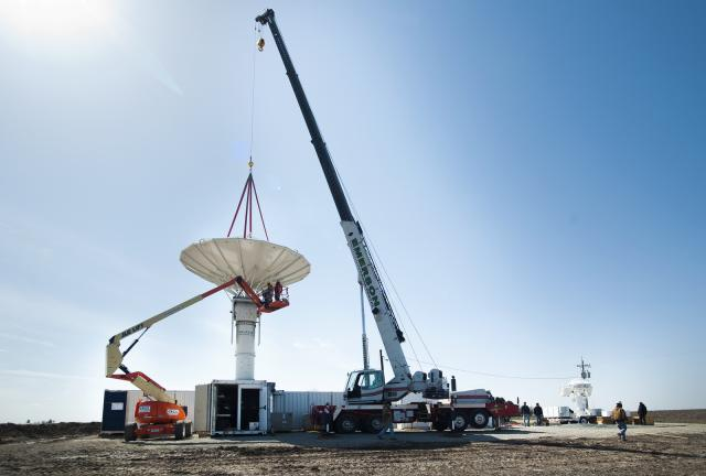 A large crane drops the NPOL antenna into place.