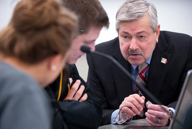 Governor Branstad works with students.