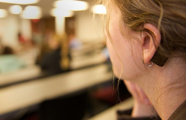 Carly Armour listens utilizing the new hearing loop installed in the Medical Laboratories building.