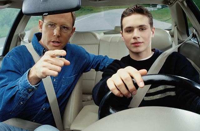 son driving a car while father offers direction